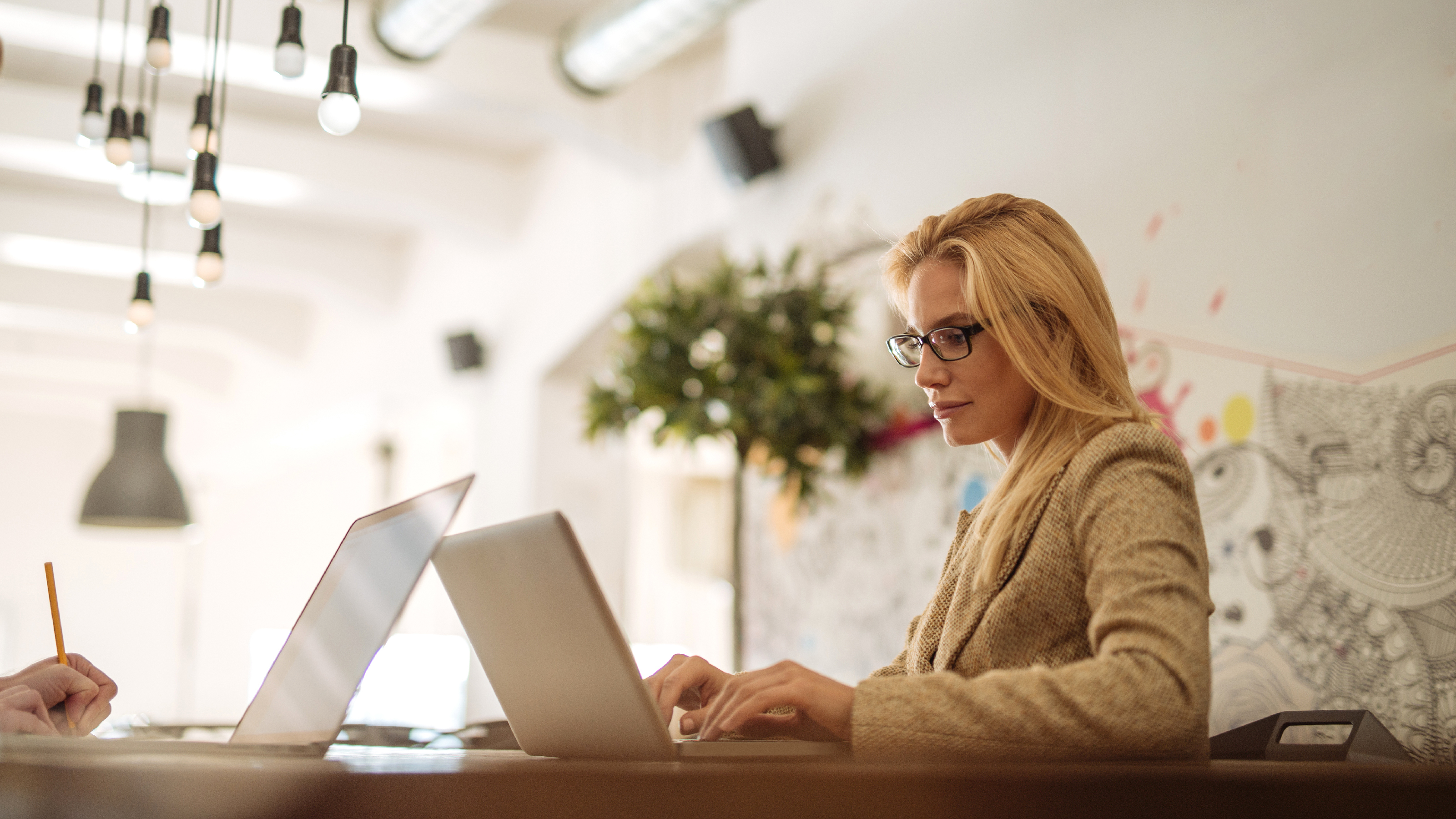 Woman wearing spectacles working on laptop